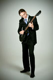 Homem formal que joga na guitarra Fotografia de Stock