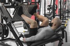 Homem forte com o corpo muscular do ajuste que faz exercícios na máquina da imprensa do pé, exercício imagens de stock royalty free