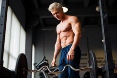 Homem forte com o corpo muscular que dá certo no gym Exercício do peso com o barbell no clube de aptidão fotografia de stock royalty free