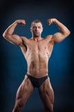 Homem forte do ajuste que demonstra seus músculos poderosos Imagens de Stock