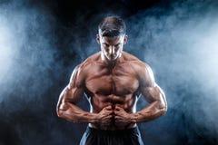 Homem forte do halterofilista com Abs perfeito, ombros, bíceps, tríceps, caixa imagens de stock