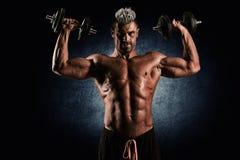 Homem forte do halterofilista com Abs perfeito, ombros, bíceps, trice imagem de stock