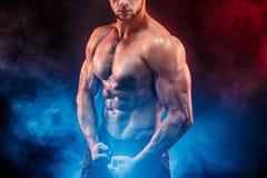 Homem forte do halterofilista em calças militares com Abs perfeitos, ombros, bíceps, tríceps, caixa imagem de stock royalty free