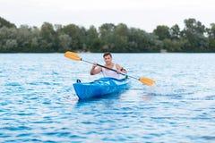 Homem forte do músculo que guarda pás ao enfileirar na canoa fotos de stock