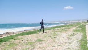 Homem forte novo Corrida da fuga Dia ventoso ensolarado Mar tormentoso vídeos de arquivo