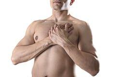 Homem forte novo do esporte do corpo com mãos em seu torso que cobre seu coração na dor no peito Imagens de Stock