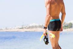 Homem forte novo que está na praia do mar Fotos de Stock