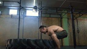 Homem forte seguro que lança o pneu grande durante o treinamento no gym video estoque
