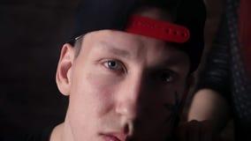 Homem fresco novo no snapback com tatuagens da cara na frente da parede de tijolo com meninas video estoque