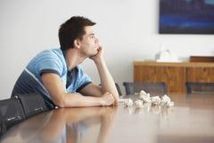Homem frustrante na tabela de conferência com papéis amarrotados Fotos de Stock