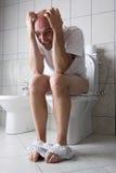 Homem frustrante no assento de toalete Foto de Stock Royalty Free