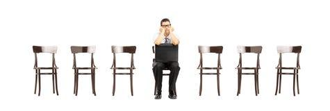 Homem furado com a mala de viagem que senta-se em um trabalho de espera da cadeira inter imagens de stock