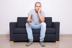 Homem furado que senta-se no sofá e na tevê de observação Fotos de Stock