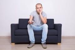 Homem furado que senta-se no sofá e na tevê de observação em casa Foto de Stock Royalty Free