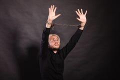 Homem furioso com mãos acorrentadas, nenhuma liberdade Foto de Stock