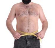Homem gordo com a fita de medição no fundo branco imagens de stock