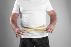 Homem gordo com a fita de medição no fundo cinzento fotografia de stock royalty free