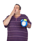 Homem gordo com um despertador azul que boceja Foto de Stock
