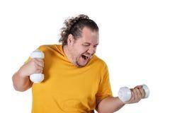 Homem gordo engraçado que exercita com pesos e que olha a câmera isolada no fundo branco fotos de stock