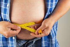 Homem gordo obeso O homem está guardando sua barriga demasiado gorda Risco sanitário da obesidade Foto de Stock Royalty Free