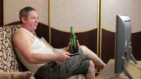 Homem gordo preguiçoso que olha a tevê quando no sofá
