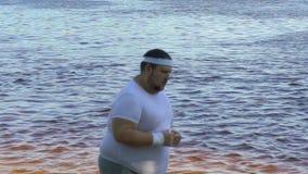 Homem gordo que corre ao longo do riverbank na manhã, programa dos weightloss, esporte vídeos de arquivo
