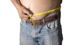 Homem gordo que guarda uma fita de medição imagem de stock