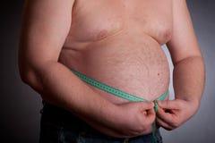 Homem gordo que prende uma fita da medida foto de stock royalty free