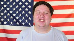 Homem gordo que ri no fundo de uma bandeira dos EUA video estoque