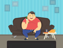 Homem gordo que senta-se em casa no sofá que olha a tevê e que bebe a cerveja Foto de Stock Royalty Free