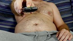 Homem gordo que usa o telecontrole da tevê filme