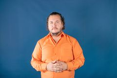 Homem gordo triste na camisa alaranjada que levanta no estúdio Problemas de saúde foto de stock