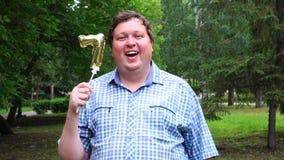 Homem grande que guarda o balão dourado que faz o número 7 exterior 7o partido da celebração do aniversário video estoque