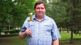 Homem grande que guarda o balão dourado que faz o 1 número exterior 1th partido da celebração do aniversário filme