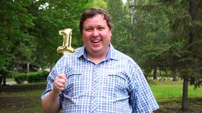 Homem grande que guarda o balão dourado que faz o 1 número exterior 1th partido da celebração do aniversário video estoque