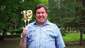 Homem grande que guarda os balões dourados que fazem o número 18 exterior 18o partido da celebração do aniversário video estoque