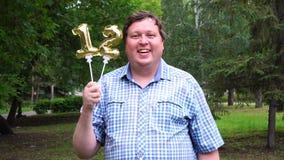 Homem grande que guarda os balões dourados que fazem o número 12 exterior 12o partido da celebração do aniversário filme