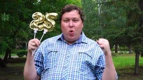 Homem grande que guarda os balões dourados que fazem o número 25 exterior 25o partido da celebração do aniversário vídeos de arquivo