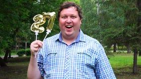 Homem grande que guarda os balões dourados que fazem o número 27 exterior 27o partido da celebração do aniversário vídeos de arquivo