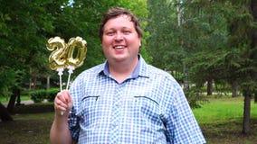 Homem grande que guarda os balões dourados que fazem o número 20 exterior 20o partido da celebração do aniversário video estoque