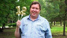 Homem grande que guarda os balões dourados que fazem o número 12 exterior 12o partido da celebração do aniversário vídeos de arquivo