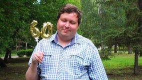 Homem grande que guarda os balões dourados que fazem o número 60 exterior 60th partido da celebração do aniversário vídeos de arquivo