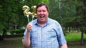 Homem grande que guarda os balões dourados que fazem o número 21 exterior 21th partido da celebração do aniversário vídeos de arquivo
