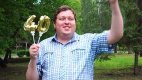 Homem grande que guarda os balões dourados que fazem o número 40 exterior 40th partido da celebração do aniversário video estoque
