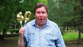 Homem grande que guarda os balões dourados que fazem o número 50 exterior 50th partido da celebração do aniversário video estoque