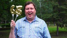Homem grande que guarda os balões dourados que fazem o número 65 exterior 65th partido da celebração do aniversário filme