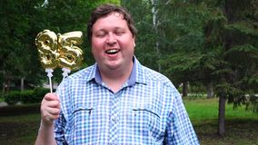 Homem grande que guarda os balões dourados que fazem o número 85 exterior 85th partido da celebração do aniversário filme