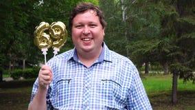 Homem grande que guarda os balões dourados que fazem o número 69 exterior 69th partido da celebração do aniversário filme