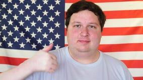 Homem grande que mostra os polegares acima no fundo de uma bandeira dos EUA Exibição do homem novo como o sinal com mão vídeos de arquivo