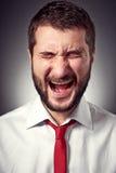Homem gritando sobre o fundo cinzento Imagem de Stock